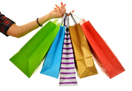 Female hand holding paper shopping bags isolated on white
