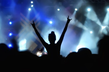 Silhouette of a girl with hand in the air on concert