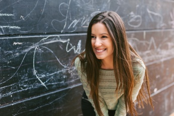Young beautiful woman standing in front a blackboard wall.